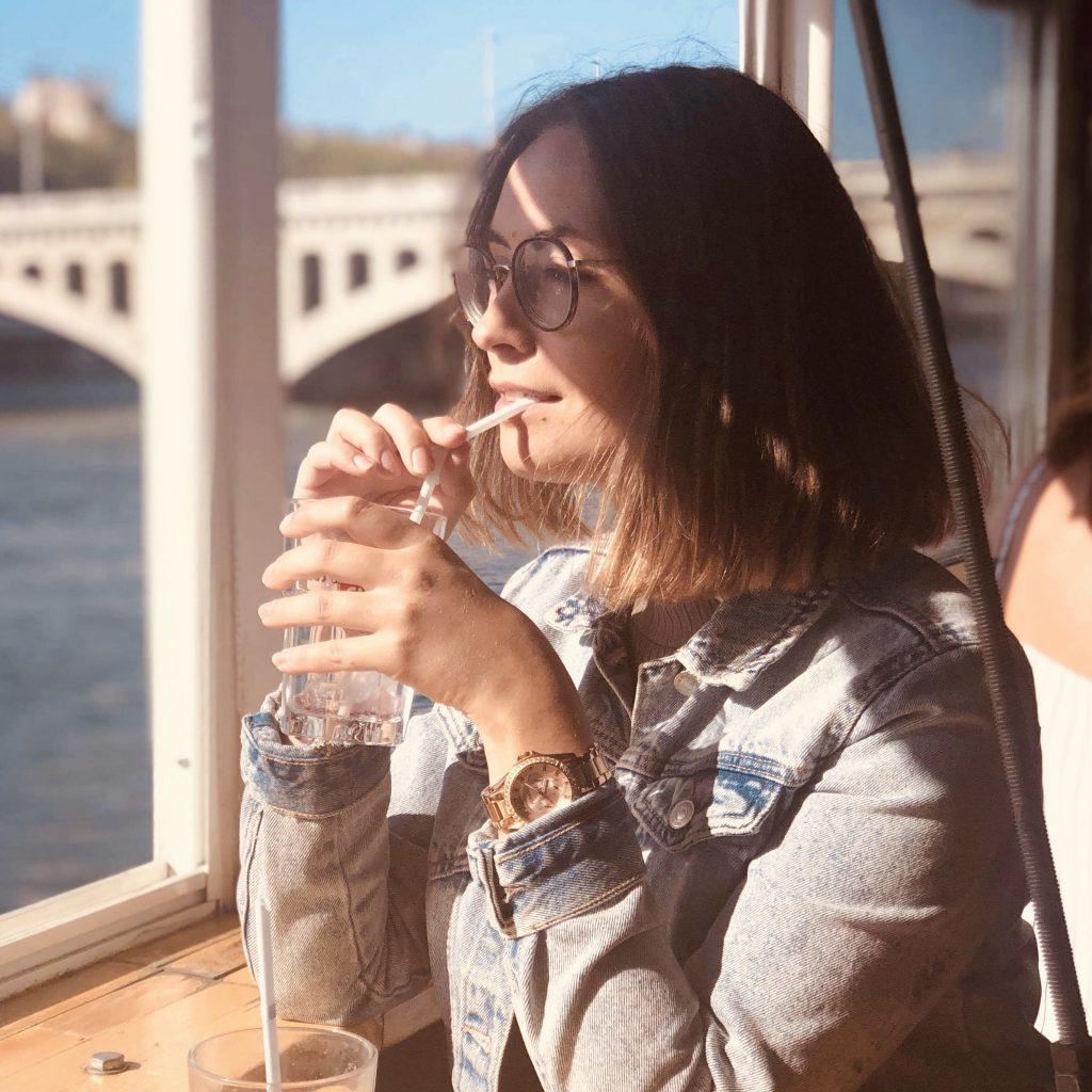 Marion boit une boisson rafraichissante sur les barques lyonnaises